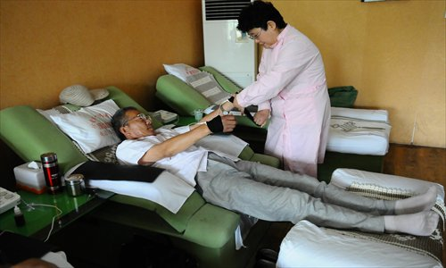 Wang Qinghua (left), a smoker from Liaocheng, Shandong Province, receives treatment at a private smoking cessation clinic on May 31. Photo: CFP