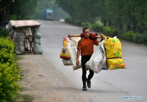 Liu Lingchao carries some bags of used bottles near his