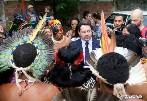A government official reads a proposal, promising to build a new museum nearby for the Indigenous people, in Rio de Janeiro, Brazil, Jan. 16, 2013. The government of Rio de Janeiro plans to tear down an old Indian museum beside Maracana Stadium to build parking lot and shopping center here for the upcoming Brazil 2014 FIFA World Cup. The plan met with protest from the indigenous groups. Now Indians from 17 tribes around Brazil settle down in the old building, appealing for the protection of the century-old museum, the oldest Indian museum in Latin America. They hope the government could help renovate it and make part of it a college for indigenous Indians. (Xinhua/Weng Xinyang)