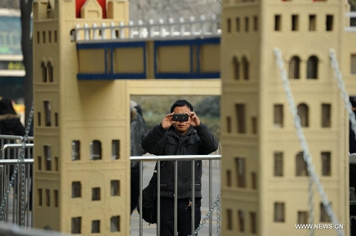 A man takes a photo of a miniature monument of the Tower Bridge on a street in Xi'an, capital of northwest China's Shaanxi Province, Jan. 10, 2013. A collection of miniatures of 10 world cultural heritages are on show here. (Xinhua/Li Yibo)