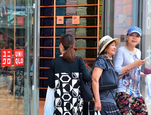 Customers shop at Japan's casual apparel retailer Uniqlo in Tokyo on Tuesday. The operator of cheap chic clothing brand Uniqlo, whose affordable garments have come to symbolize deflation-plagued Japan, said it will hike its prices by 5 percent, blaming a weaker yen and climbing procurement costs. Photo: AFP