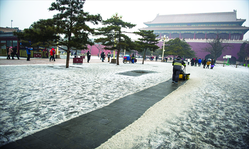 A cleaner clears a path through the snow in front of Duanmen, one of the main gates of the Forbidden City, Thursday. Photo: Li Hao/GT