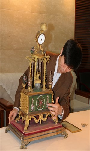 A Forbidden City museum expert studies an antique clock on Sunday that was damaged when a vandal smashed a window. Photo: Courtesy of the Forbidden City