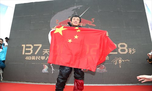 A weary but victorious Guo Chuan holds up a flag after completing his single-handed sail around the world.