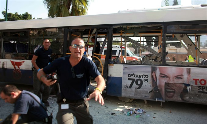 Israeli police gather after a blast ripped through a bus near the defense ministry in Tel Aviv on Wednesday. At least 21 people were injured, in what an official said was