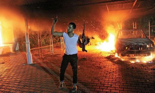 An armed man waves his rifle as buildings and cars are engulfed in flames after being set on fire inside the US consulate compound in Benghazi late Tuesday. An armed mob attacked the US consulate in Benghazi and set fire to the building. Photo: AFP
