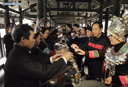 People of the Dong ethnic group attend a feast during a celebration ceremony marking the 100th anniversary of the completion of Chengyang Fengshui Bridge held in Sanjiang Dong Autonomous county, South China's Guangxi Zhuang Autonomous Region, December 1, 2012. Built in 1912, the 77.76-meter-long bridge is famed for its combination of bridge, veranda and Chinese pavilion. (Xinhua/Lai Liusheng)