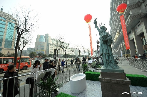 A miniature monument of the Statue of Liberty is seen on a street in Xi'an, capital of northwest China's Shaanxi Province, Jan. 10, 2013. A collection of miniatures of 10 world cultural heritages are on show here. (Xinhua/Li Yibo)
