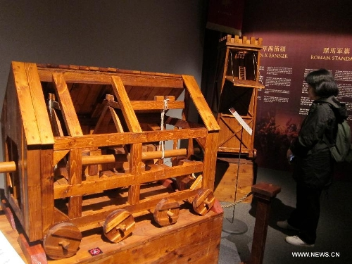 A visitor reads the introduction of the model of a Rome siege weapon during an exhibition at Hong Kong Science Museum in south China's Hong Kong, Jan. 23, 2013. Exhibition
