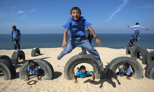 Palestinian school children play with tyres on Gaza beach on Thursday in Deir al-Balah. Photo: AFP
