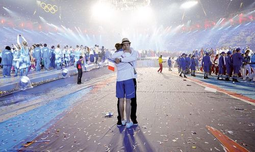 Two athletes hug during the athletes parade at the closing ceremony of the 2012 London Olympic Games in London on Sunday. Rio de Janeiro will host the 2016 Olympic Games. Photo: AFP