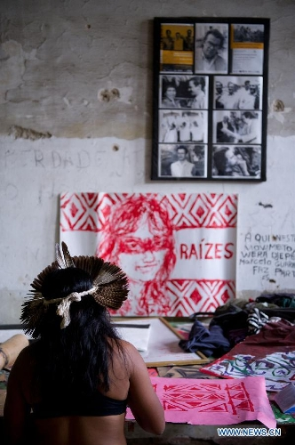 An indigenous woman draws traditional patterns inside the old Indian Museum in Rio de Janeiro, Brazil, Jan. 16, 2013. The government of Rio de Janeiro plans to tear down an old Indian museum beside Maracana Stadium to build parking lot and shopping center here for the upcoming Brazil 2014 FIFA World Cup. The plan met with protest from the indigenous groups. Now Indians from 17 tribes around Brazil settle down in the old building, appealing for the protection of the century-old museum, the oldest Indian museum in Latin America. They hope the government could help renovate it and make part of it a college for indigenous Indians. (Xinhua/Weng Xinyang)