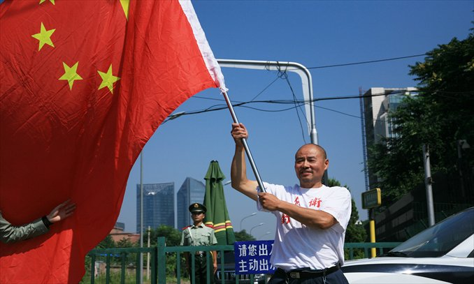 An activist holds up a Chinese flag outside the Japanese embassy in Beijing on Wednesday claiming sovereignty over the Diaoyu Islands. Photo: Guo Yingguang/GT
