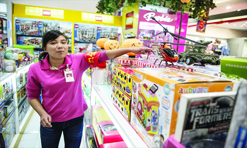 A staff member holds a model helicopter in New World Department Store, Chaoyang district Monday. Customers must temporarily show ID before purchasing a model aircraft in Beijing. Photo: Li Hao/GT