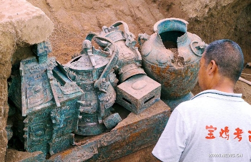 File photo taken on July 5, 2012 shows ancient bronze artifacts unearthed from the Shigushan Mountain of Baoji City, northwest China's Shaanxi Province. Archaeologists said Sunday that one piece of thigh armor and two pieces of upper-body armor dating back 3,000 years may be the oldest pieces of bronze armor ever unearthed in China. The announcement was made after experts studied the artifacts retrieved from the tomb of a nobleman from the West Zhou Dynasty (1046 BC - 771 BC) in Shigushan Mountain of Baoji City. Liu Junshe, head of the excavation team, said the discovery filled in a blank in China's early military history, as excavations of pieces of armor forged during or prior to the Qin Dynasty (221 BC - 206 BC) have been rare. (Xinhua/Feng Guo)
