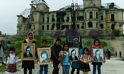 Afghan children pose for a photograph holding images of victims of war during a memorial ceremony in front of the destroyed palace of Darul Aman in Kabul on Friday. Activists and survivors gathered to pay tribute to the memory of those killed during the last three decades of war in Afghanistan. Photo: AFP