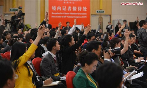 Journalists raise hands to ask questions during a group interview, with its theme
