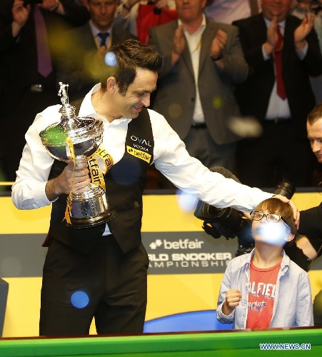Ronnie O'Sullivan (L) of England celebrates with his son Ronnie Junior during the awarding ceremony for 2013 World Snooker Championship at the Crucible Theatre in Sheffield, Britain, May 6, 2013. Ronnie O'Sullivan sealed his fifth world title by defeating Barry Hawkins of England with 18-12 in the final. (Xinhua/Wang Lili)