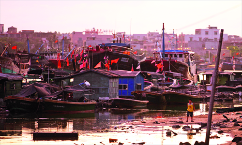 Boats and buildings at the Tanmen port take on a pink glow in the setting sun. Photo: Cai Xianmin/GT