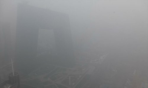 File photo: Buildings are shrouded in fog near the Guomao Bridge in Beijing, capital of China, January 23, 2013. Photo: Xinhua