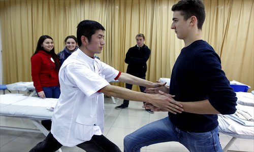 A Chinese instructor shows students the correct posture for tuina massage therapy. Photos: Yang Hui/GT