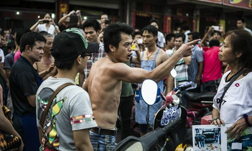 A restaurant owner gestures at animal rights activist Du Yufeng during a verbal fight in Yulin, South China's Guangxi Zhuang Autonomous Region on June 21, locally known as