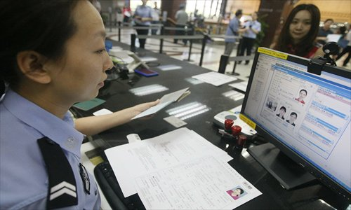 The Beijing Exit-Entry Administration Department serves a resident who is applying for a passport. Photo: CFP