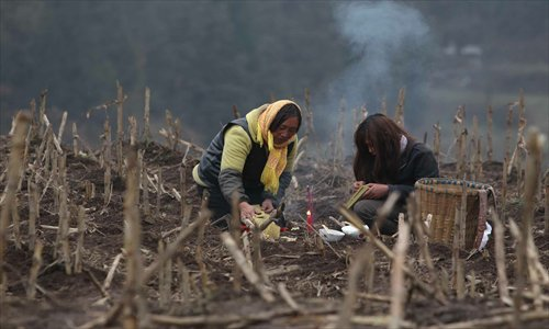Villagers light candles during a memorial service for their loved ones who were killed by a landslide Friday in Zhenxiong county, Yunnan Province that claimed the lives of 46 people. Photo: CFP