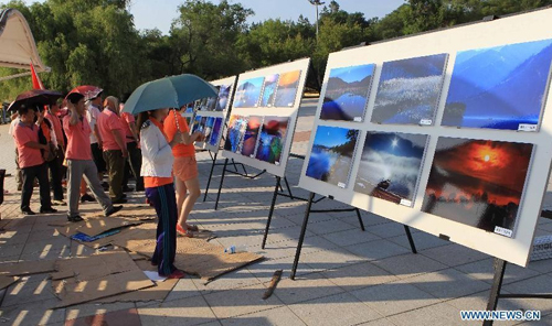 Tourists view photos about the Jingpo Lake at the Jingpo Lake scenic area in Mudanjiang, northeast China's Heilongjiang Province, July 7, 2012. About 30 percent more tourists have visited the Jingpo Lake scenic area this year than the same period last year, following a series of promotions. Photo: Xinhua