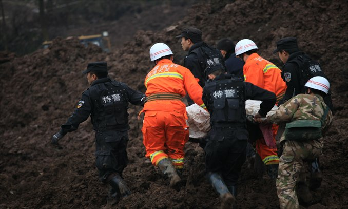 Rescuers and special police carry the body of  a victim of the landslide in Zhenxiong county, Yunnan Province on Friday. At least 46 people are believed to be buried under the landslide in the mountainous region in the morning and 42 were confirmed dead by press time. Photo: CFP