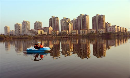 People go boating Saturday on a lake in Poyang county, East China's Jiangxi Province, with a new housing project in the background. Photo: CFP