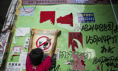 An animal rights advocate puts up a poster that calls for people not to eat dogs and cats. Photo: Li Hao/GT