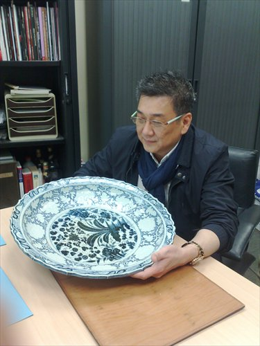 Preeminent dealer William Chak appreciates a blue and white Yuan Dynasty (1279-1368) ashet at a 2011 pre-auction exhibition. Photo: Courtesy of Chak's Company Limited