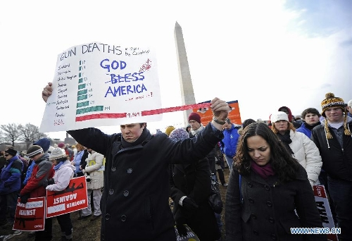 People hold signs against gun violence in front of the Washington Monument during a march in Washington D.C., capital of the United States, Jan. 26, 2013. Thousands of people, including family members of victims and survivors of shootings at Virginia Tech University, Sandy Hook elementary school and others, took part in a march for stricter gun control laws here on Saturday. (Xinhua/Zhang Jun)
