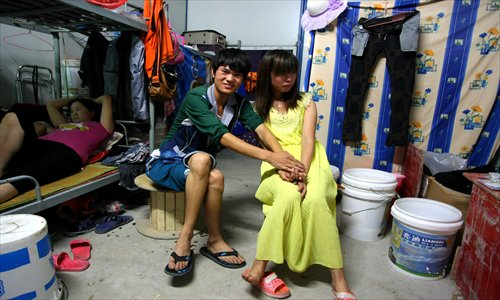 Wu Jianguo and his shy wife sit in the accomodation which they share with three other couples. Photo: Yang Hui/GT