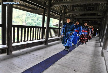 People of the Dong ethnic group walk through the Chengyang Fengyu Bridge during a celebration ceremony marking the 100th anniversary of its completion held in Sanjiang Dong Autonomous county, South China's Guangxi Zhuang Autonomous Region, December 1, 2012. Built in 1912, the 77.76-meter-long bridge is famed for its combination of bridge, veranda and Chinese pavilion. (Xinhua/Lai Liusheng)