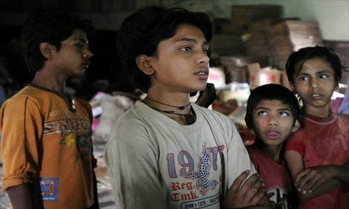 Nepalese children look on during an inspection by authorities of saree embroidery factories in Thimi on the outskirts of Kathmandu on Wednesday. Hundreds of underage children have been found to be working in the factories, where they were alleged to be working in excess of 12 hours daily in squalid conditions. Photo: AFP