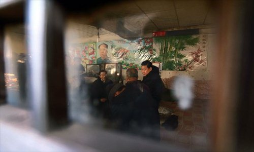 Xi Jinping (R), general secretary of the Communist Party of China (CPC) Central Committee and chairman of the CPC Central Military Commission, visits the family of Gu Chenghu, an impoverished villager in the Gujiatai Village of Longquanguan Township, Fuping County, north China's Hebei Province, Dec. 30, 2012. Xi made a tour to impoverished villages in Fuping County from Dec. 29 to 30, 2012. Photo: Xinhua