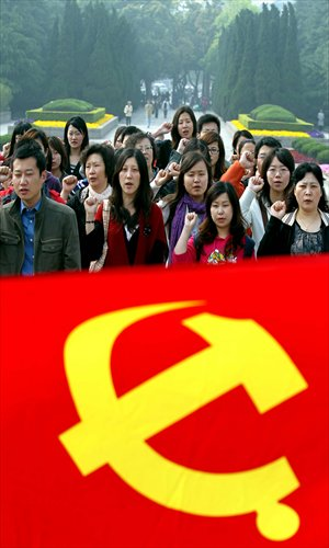 Party members from foreign companies swear an oath by a Communist Party of China flag at a cemetery for revolutionary martyrs in Shanghai on April 24. The activity was organized by the Shanghai Foreign Service Co. Photo: Xinhua
