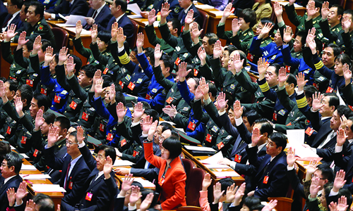 Delegates raise their hands to show approval for a work report at the closing ceremony of the 18th Party congress held at the Great Hall of the People Wednesday. Photo: IC