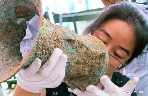 File photo taken on July 5, 2012 shows an archeologist checking engravings on an unearthed bronze artifact in the Shigushan Mountain of Baoji City, northwest China's Shaanxi Province. Archaeologists said Sunday that one piece of thigh armor and two pieces of upper-body armor dating back 3,000 years may be the oldest pieces of bronze armor ever unearthed in China. The announcement was made after experts studied the artifacts retrieved from the tomb of a nobleman from the West Zhou Dynasty (1046 BC - 771 BC) in Shigushan Mountain of Baoji City. Liu Junshe, head of the excavation team, said the discovery filled in a blank in China's early military history, as excavations of pieces of armor forged during or prior to the Qin Dynasty (221 BC - 206 BC) have been rare. (Xinhua/Feng Guo)