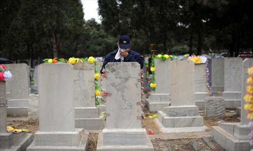A resident pays tribute and weeps in front of a tombstone at the Babaoshan People's Cemetery in Beijing. Photo: CFP