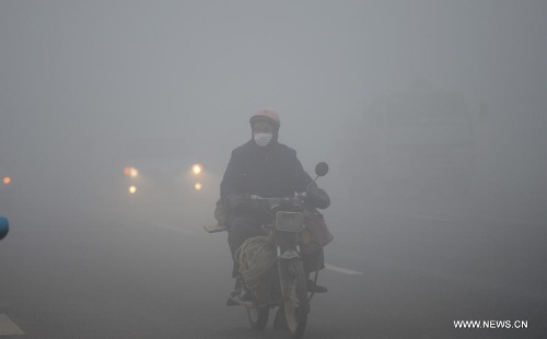 A citizen rides amid dense fog in Nanchang City, capital of east China's Jiangxi Province, Jan. 12, 2013. A fog hit many parts of Jiangxi on Saturday. (Xinhua/Zhou Ke)