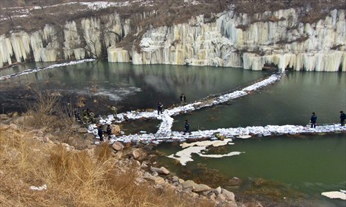 Workers build a network of dams made of activated carbon to intercept aniline from flowing downstream at the border of Hebei, Henan and Shanxi provinces Monday, after some 9 tons of aniline was leaked from a chemical plant in Shanxi on December 31. Photo: CFP