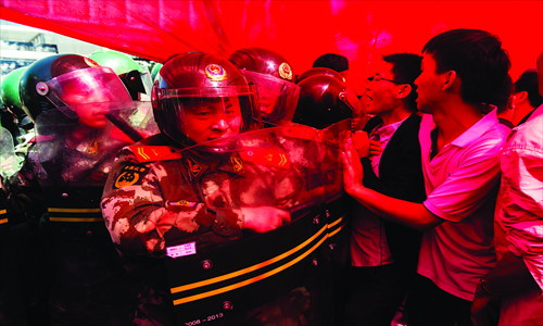 Protesters face armed police in front of the Japanese embassy in Beijing on Saturday. Photo: Li Hao/GT