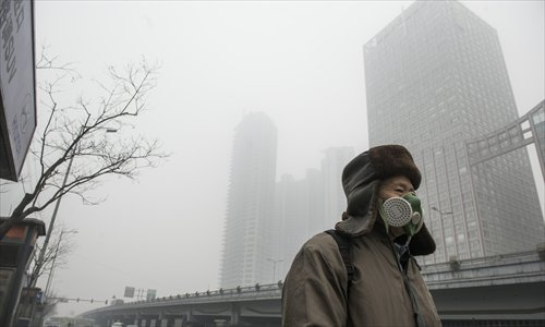 A man wearing a mask walks along a smog-shrouded street in Beijing, the capital of China, on January 29, 2013. The National Meteorological Center (NMC) issued a code-blue alert on January 27 as the smoggy weather forecast for the following two days would cut visibility and worsen air pollution in some central and eastern Chinese cities. Photo: Li Hao/GT