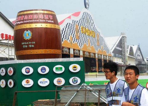 Staff members walk past a beer house to be used in the 22nd Qingdao International Beer Festival in Qingdao, a coastal city in East China's Shandong Province, August 7, 2012. The 22nd Qingdao International Beer Festival, which will last from August 11 to August 26, has attracted 25 famous beer brands from 16 countries and regions. Photo: Xinhua