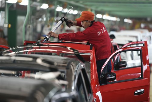 An employee works on an electronic vehicle at a factory in Zouping, East China's Shandong Province. Photo: CFP