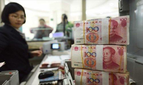 A bank staff member checks RMB banknotes at a bank in Lianyungang, east China's Jiangsu Province, January 7, 2016. Photo: Xinhua