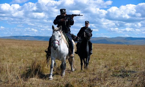A mounted policeman aims his rifle. Photo: CFP